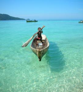enfant dans un canoë sur une mer turquoise translucide