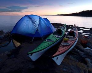 Une tente et 2 kayaks au bord de l'eau au crépuscule