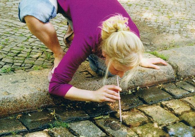 Femme qui boit l'eau du troitoire